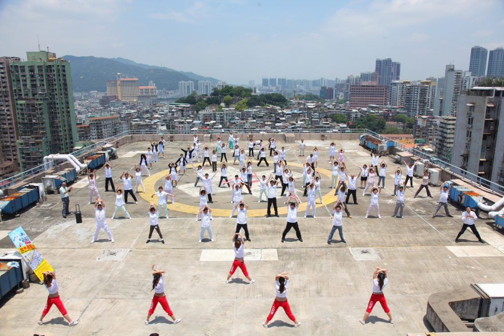 More than 80 people take part in group exercise on a high-rise rooftop during the TAFISA World Challenge Day in Macau, China.