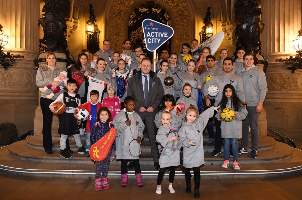 Hamburg politicians in charge of sports delivery pictured with a group of young sports players from the city.