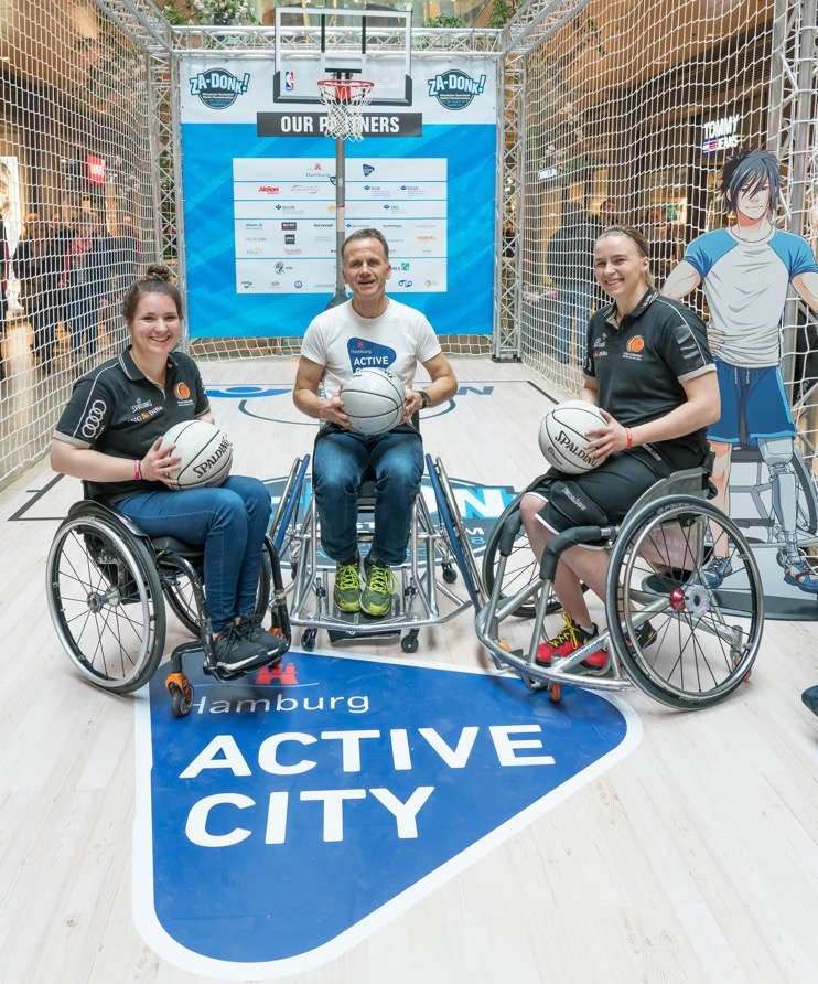 State Councillor Christoph Holstein tries wheelchair basketball with two national players.