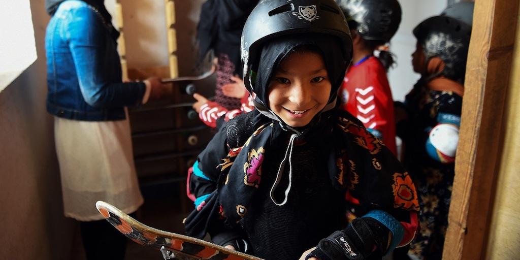 A smiling girl holding her skateboard.
